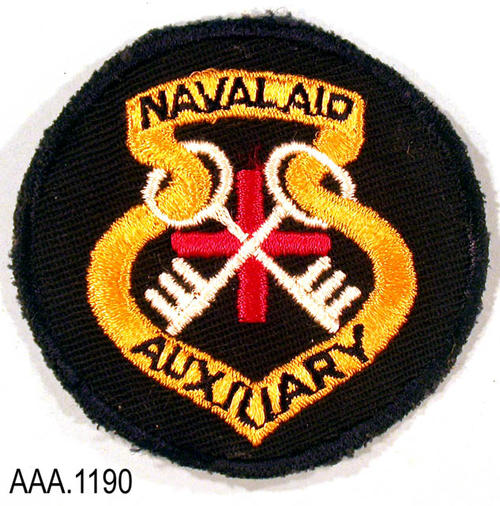 "This artifact is a patch to be worn on a uniform.  It is dark blue.  The dark blue text is printed on a gold design and reads:  "" NAVAL AID AUXILIARY."" In the center of the design is a red plus sign with two white keys that are crossed.  This patch measures 2 3/4"" in diameter."