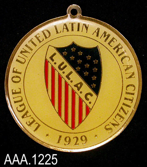 "This artifact is a round, gold, pendant.  Gold text on a white background around the edge reads:  ""League of United Latin American Citizens - 1929 -.""  In the center of the pendant is a shield with the initials, ""L.U.L.A.C."" going diagonally across the front.  Gold stars on a blue field make up the upper right portion of the shield while red and white stripes the lower left side of the shield.  This artifact measures 1 5/8"" in diameter."