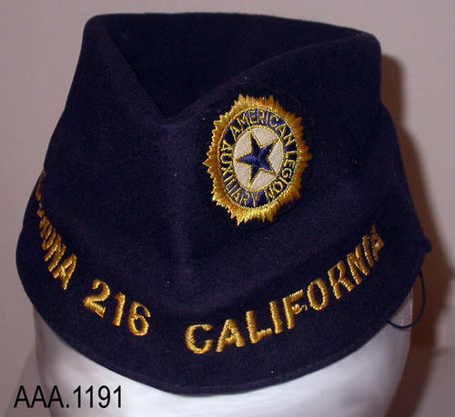 "This artifact is a dark blue, American Legion hat.  Text embroidered on the front of the cap in gold colored  thread reads:  ""Corona - 216 - California.  Above the text on one side of the cap is the American Legion Auxiliary patch.  This cap measures 10 1/2"" x 3 3/4""."