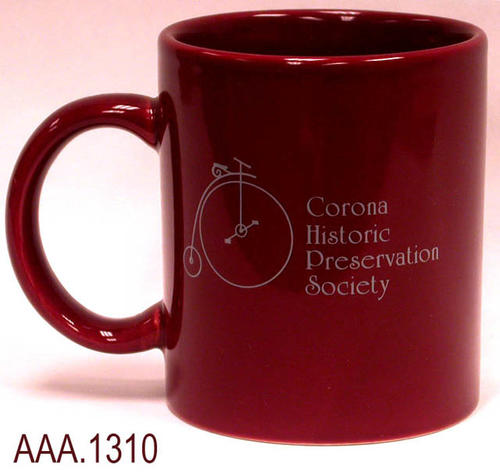 "This artifact is a dark, rust colored coffee mug.  The following is imprinted on the side of the mug in a gray color.   First is the outline of an old-fashioned bicycle and the following text:  ""Corona Historic Preservation Society."""