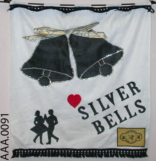"This artifact is a 45.5 x 36 inch banner.  It is made of white felt with black fringe and ribbon.  Shown on the banner are two black bells with silver sequins and a gold bow.  Two dancers appear in the lower left corner, and ""Silver Bells,"" in black felt is in the middle. The Cow Counties hoedown association emblem is in the lower right hand corner.  CONDITION:  Good"