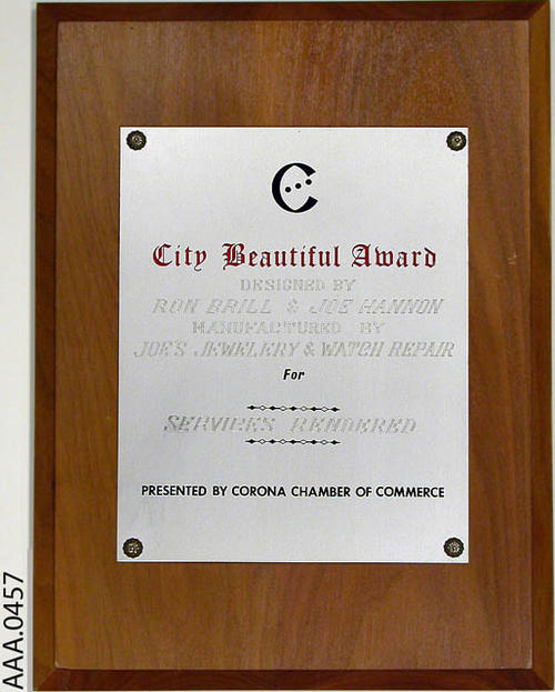 This artifact is a City Beautiful Award in the form of a plaque.  It was presented by the Corona Chamber of Commerce. The plaque was designed by Ron Brill and Joe Hannon.