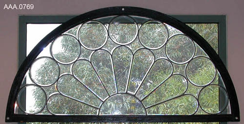 This artifact is a half-circle, leaded glass window with half daisy and circles bordering  petals.  CONDITION:  Good. Donor's Remarks:  This artifact was formerly installed in the Independent Order of Odd Fellows Temple at 614 S. Main Street, Corona, California in 1902.  The building was demolished in 1969 for urban renewal.  This window is currently installed in the Heritage Room at the Corona Public Library on the north wall.