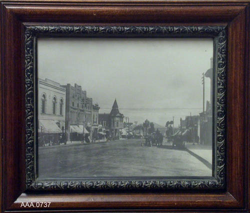 "This artifact is a B/W photo of Main Street Corona.  The back of the photo reads, ""In Appreciation to Mr. Addison, Heritage Committee Chairman, 1978-1983.""  This photo measures 13 1/2"" x 11 3/4""."