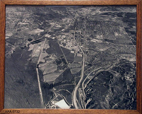 "This artifact is a framed, B/W, aerial photograph covering Home Gardens, the 91 Freeway, the airport, Norco, and Temescal Canyon.  It measures 21"" x 17""."