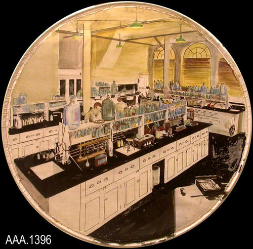 This artifact is round, watercolor art depicting a Chemistry Lab.  This was done by Mr. Howard Mullins, the art teacher at Corona Sr. High School in the 1930's and 1940's.  The series of six pictures, depicting various Corona-Norco scenes, were possibly used during the Golden Jubilee in 1936.  Each watercolor was done on linen and then sewn to a round metal hoop.