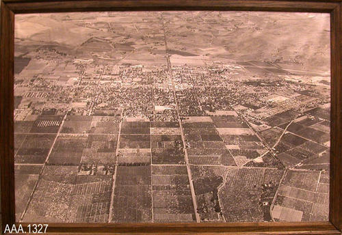 "This artifact is a framed aerial photograph.  Text on the back of the artifact reads:  ""Aerial View of Corona, Calif. - Taken August 1, 1957 - (Donated August 1, 2005 - In Memory of - George G. Grover).  This artifact measures 38 1/2"" x 26 1/2""."