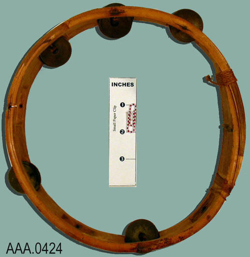 This artifact is a bamboo tambourine.  It is bound with string.  It has metal rods holding eleven coin noisemakers of Spanish origin. Donor's Remarks:  This tambourine was probably brought back by Elmer Fern Gleanson when he was in the Philippines during the Spanish American War.