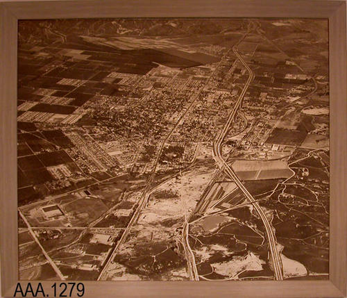 This artifact is a framed, aerial photograph of a section of Corona showing the 91Freeway.