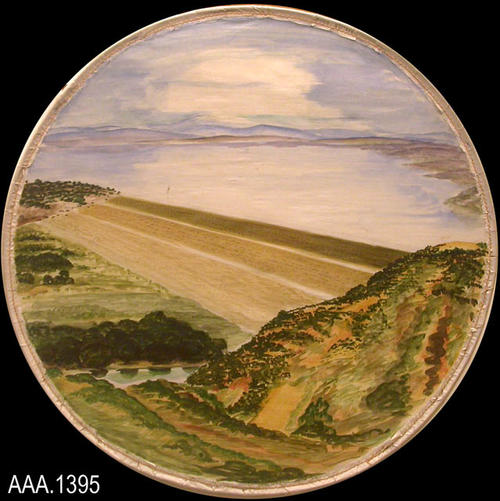 This artifact is round, watercolor art depicting a Scenic View from the Hills.  This was done by Mr. Howard Mullins, the art teacher at Corona Sr. High School in the 1930's and 1940's.  The series of six pictures, depicting various Corona-Norco scenes, were possibly used during the Golden Jubilee in 1936.  Each watercolor was done on linen and then sewn to a round metal hoop.