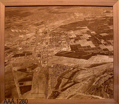 "This artifact is a large, framed, aerial photograph showing a section of Corona where the 91 Freeway goes through the city.  This framed photograph measures 83 1/2"" (W) and 73 5/8"" (H)."