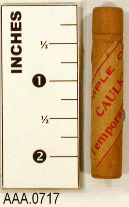 This artifact is an empty container for a sample of Caulk's temporary stopping.