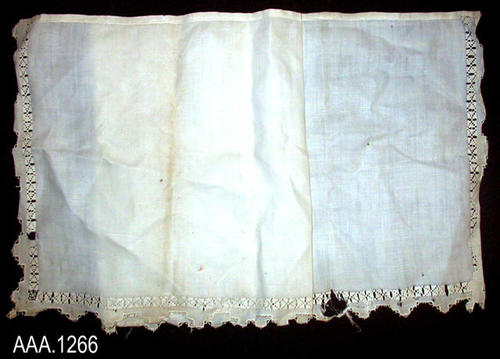 "This artifact is a white, linen, tablecloth. There is lace on three sides.  It measures 64 1/2"" x 21 1/2"".  CONDITION:  The fabric of this tablecloth has numerous, small, brown spots as well as small holes."