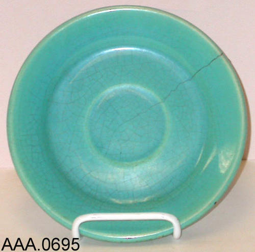 This artifact is a turquoise saucer, probably used under a coffee cup.  It was made in Corona.