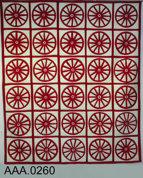 This artifact is a Friendship Quilt.  It was made by the Baptist Church Quilters.  It has a red border, wheels, and spokes on a white background. On the white background between the red spokes, names are written in black.