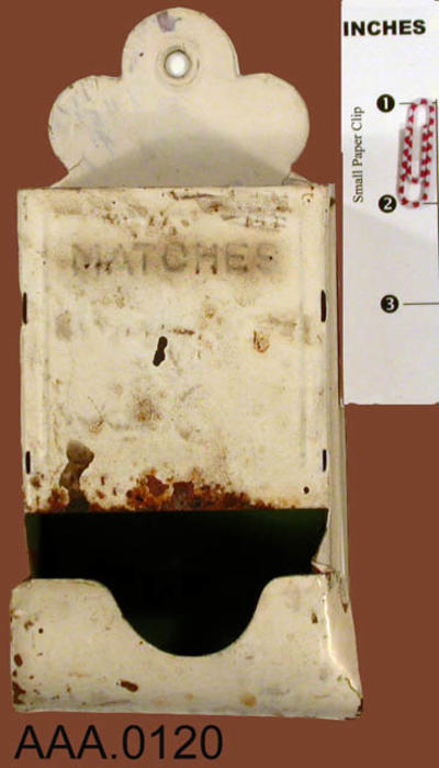 "This artifact is a box shaped, stick match holder, painted white with the word ""Matches' on the front of the holder.  CONDITION:  This artifact is in poor condition. CONDITION:  Rust is coming through the white paint."
