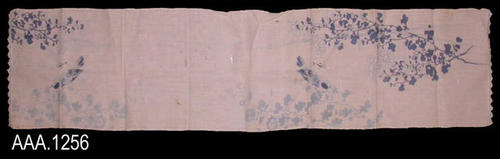 This artifact is a white, linen, table runner with blue flowers and blue colored birds making the design.  On each end of the runner is a scalloped, lace border.  CONDITION:  This artifact has several, small, brown stains and some nine holes in the fabric.