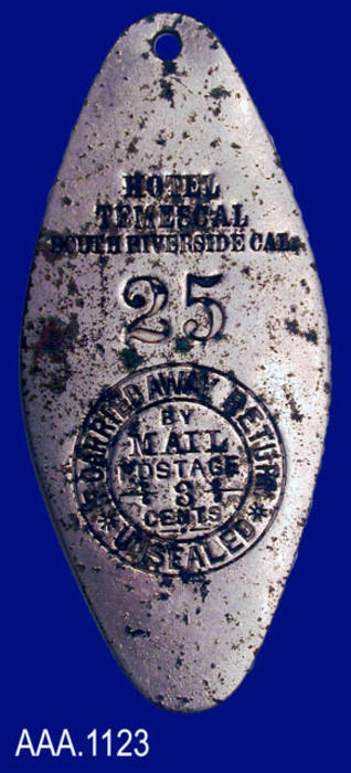 "This artifact is a metal key holder for a key to Room 25 in  the Temescal Hotel. Text imprinted in a circle reads:  ""IF CARRIED AWAY RETURN - UNSEALED - BY MAIL - POSTAGE 3 CENTS."""