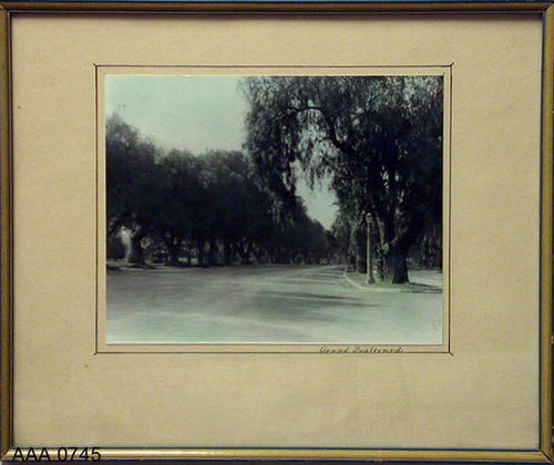 "This artifact is a framed B/W print that has been lightly hand colored. It depicts Grand Blvd. in Corona, California.  This artifact measures 15 1/2"" x 12 3/4""."