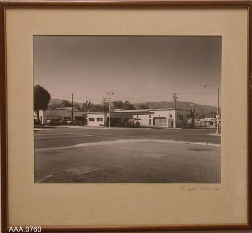 "This artifact is a framed B/W photograph of a Corona street corner with a 76 Service Station and Cole Buick.  This framed artifact measures 18"" x 16 1/4""."