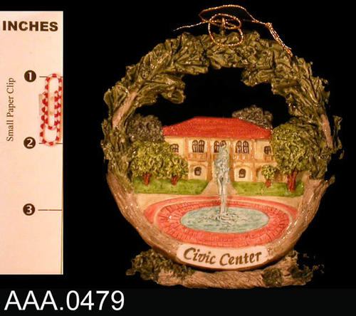 This artifact is one ornament of the Corona Civic Center circled by tree limbs.