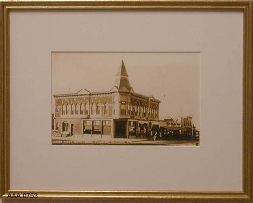 This artifact is a gold-framed B&W photograph of the 1st National Bank building in Corona, California.  It was in this building that the first Corona library was housed.