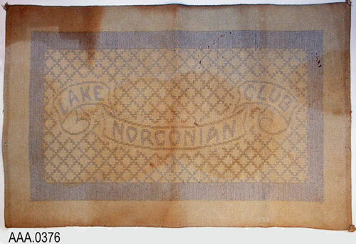 This artifact is a bath mat from the Lake Norconian Club circa 1929.  Was in the home of Juanita Bachand. This artifact measures 33 x 21 inches.