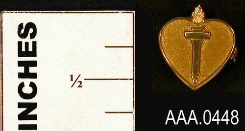 This artifact is a gold, heart shaped pin with a torch in the middle of the pin.