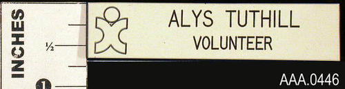 "This artifact is a  white name tag.  It has the following text:  ""Alys Tuthill, Volunteer."""