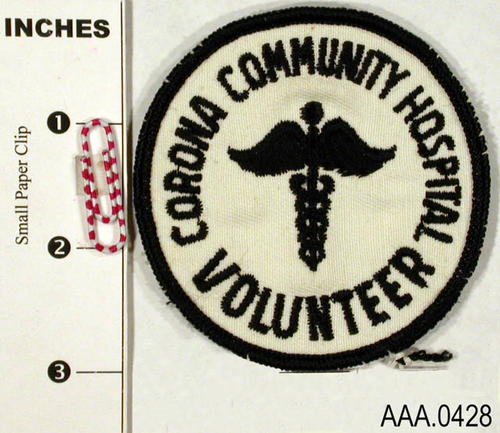 "This artifact is a  volunteer patch.  It is circular with a white background and black letters that read:  ""Corona Community Hospital Volunteer"" Donor's Remarks:  This patch was worn by Alys Tuthill on her pink jacket while acting as a ""Pink Lady Volunteer"" at the old community hospital."