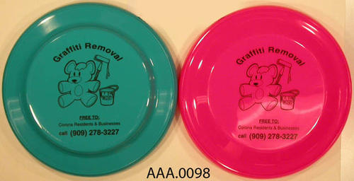 "This artifact collection consists of one blue and one pink frisbee inscriped with:  ""GRAFFITI REMOVAL"" on top."