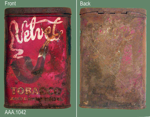 "This artifact is a tin of Velvet Tobacco.  On the front in text simulating rising smoke is the word, ""Velvet,"" coming up from the bowl of the pipe.  The text and design on the back of the tin has been obliterated.  CONDITION:  This artifact is very rusty and in poor condition. DONOR'S REMARKS:  This artifact was removed from the Tuthill home on W. Main Street prior to demolition."