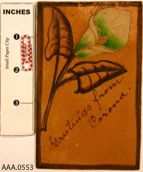 "This artifact is a dark green, leather postcard with a painted velvet lily appliqued on it.  The text reads:  ""Greetings from Corona"" is written across the front in script and ""Postcard"" is stamped in ink on the reverse."