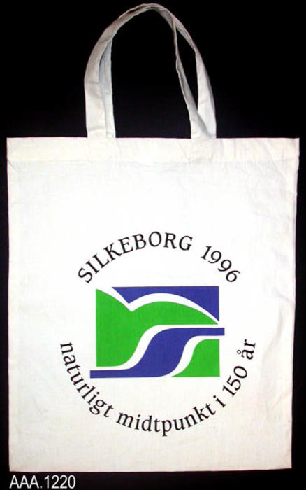"This artifact is a white cloth bag with handles.  It is from Silkeborg, Denmark, one of Corona's Sister Cities.  The following inscription is on one side of the bag:  ""Silkeborg 1996, Naturligt Midtpunkt; 150 ar.""  This bag measures 14"" x 16""."