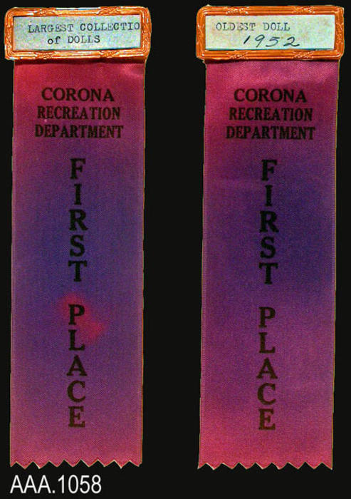 "This artifact collection consists of two blue ribbons that are beginning to fade to purple.  At the top of each ribbon is a metal pin that holds the title for the event.  One of the events is for the, "" Largest Collection of Dolls,""  the other is for the, ""Oldest Doll 1952.""  The text on each ribbon is identical and reads, ""Corona Recreation Department - First Place."" CONDITION:  The ribbons are changing color and are regarded to be in fair condition."