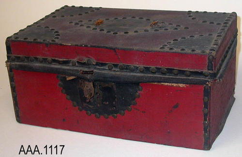 "This artifact is a small red and black hand trunk with round tacks used to attach the trim.  C. 1860.  This trunk measures:  12"" (L), 7"" (W), 5"" (H).  CONDITION:  The lid of this trunk is attached by a small leather strap.  The covering is in dissaray. Donor's Remarks:  This trunk belonged to Albert Farmers grandfather during the Civil War."