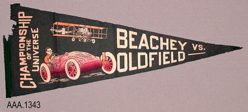 "This artifact is a dark green, triangular shaped, felt banner.  The white text on the banner reads:  ""Champions of the Universe - Beachey vs. Oldfield.""  The banner also has two graphics: (1) The Wright Bros. airplane, (2) a race car.  This banner measures 29"" (L) and 11 1/4"" at the widest portion of the triangle."