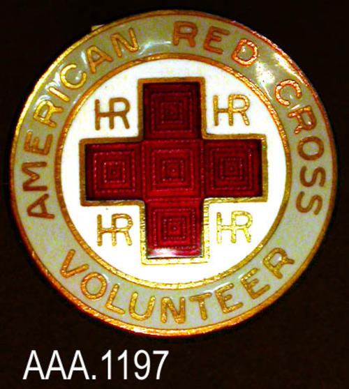 "This artifact is a Red Cross pin that is 7/8"" in diameter.  The pin has a white background and a gray border with a red cross in the middle.  The text reads:  ""American Red Cross - Volunteers."" Donor's Remarks:  This pin belonged to the donor's mother.  She was a Red Cross ""Gray Lady."""