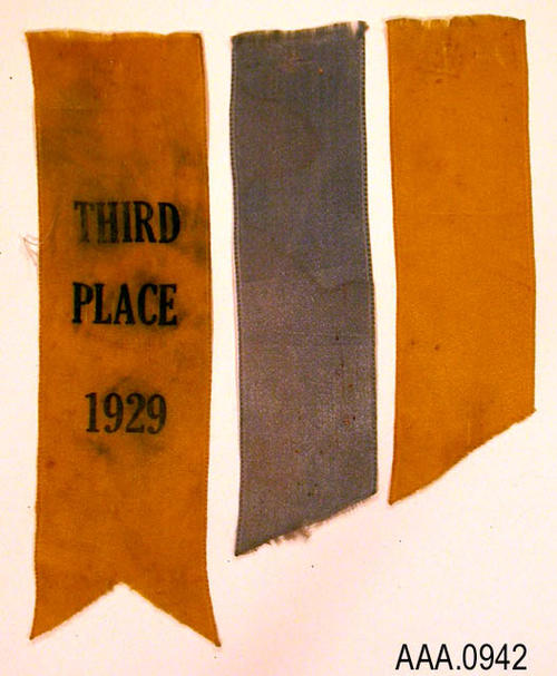 "This artifact is a gold and blue award ribbon in three parts.  The text imprinted on the ribbon reads as follows:  ""Third Place - 1929.""  The text ribbon measures 5 1/4"" x 1 1/2""."