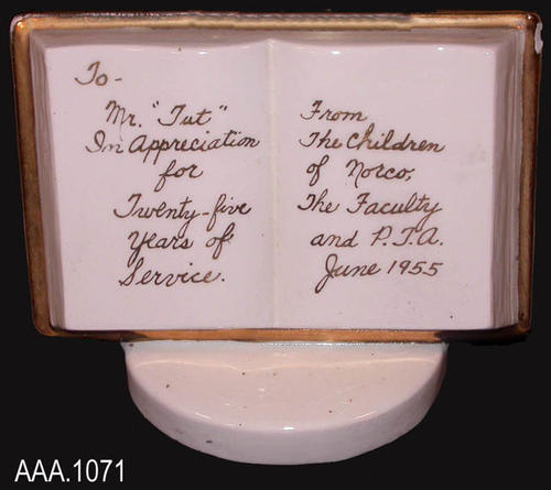 "This artifact is a commerative piece shaped like an open book.  It is white with gold trim.  The text reads:    To- Mr. ""Tut"" In appreciation for twenty-five years of service.  From the children of Norco, the faculty and P.T.A. June 1955.""  CONDITION:  The only noted damage is a chip on the top right corner."