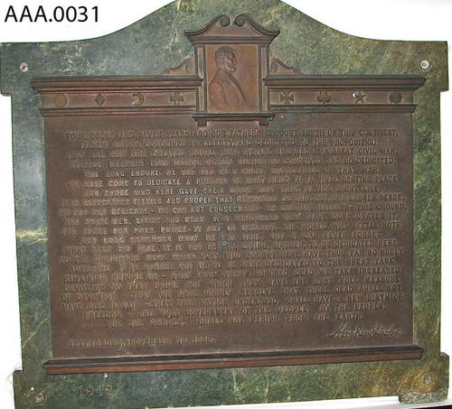 This artifact is a bronze plaque mounted on green marble with a relief of Abraham Lincoln's portrait and his Gettysburg Address.  The dates 1912 and 1913 appear on the bottom left and right, respectively, of the mounting.  This artifact is very heavy. CONDITION:  There is a crack in the green marble on the upper right hand side.