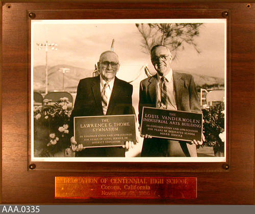 This aftifact is a plaque with a picture of Lawrence G. Thome holding a plaque for the Lawrence G. Thome Gymnasium and Louis Vander Molen holding a plaque for the Louis Vandermolen Industrial Arts Building for Centennial High School.