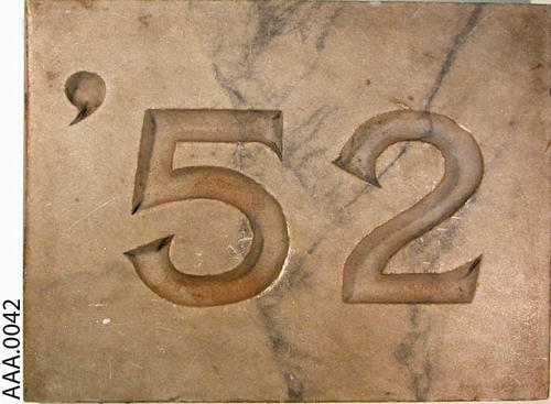 "This artifact is a 12 "" by 9 "" marble slab with the class year '52 on it."
