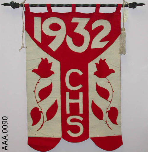 This artifact is a  red and white, 1932 Corona High School felt banner with a black iron hanger.