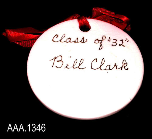 "This artifact is a white, ceramic name tag with gold text.  At the top of the tag is a red ribbon and on the back of the ribbon is a safety pin to attach the tag to clothing.  The hand written, gold, cursive text reads as follows:  "" Class of ""32"" - Bill Clark.""  This tag measures 2 1/2"" in diameter."
