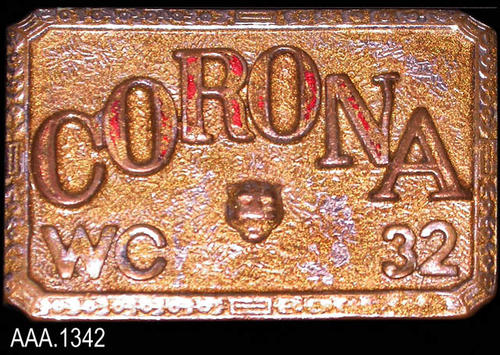"This artifact is a silver colored belt buckle with the following text on the front:  ""CORONA - WC - 32.""  In the center of the belt buckle is a small image of a panther, the mascot for Corona High School."