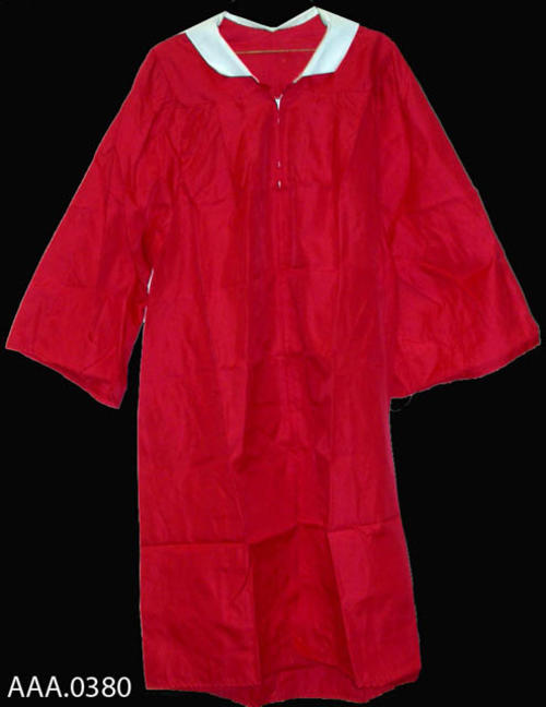 This artifact is a Corona High School Graduation Robe.  The robe is red with a white collar and is from the Class of 1983.