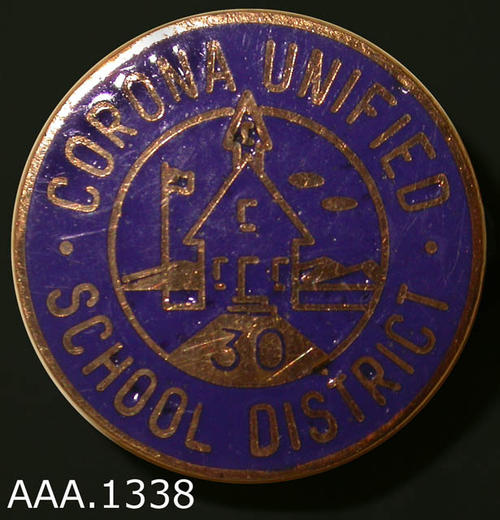 "This artifact is a small thirty year pin measuring 1/2"" in diameter.  The background is dark blue with gold colored text which reads:  ""Corona Unified - School District.""  In the center of the pin is a small schoolhouse and flag with a ""30."""