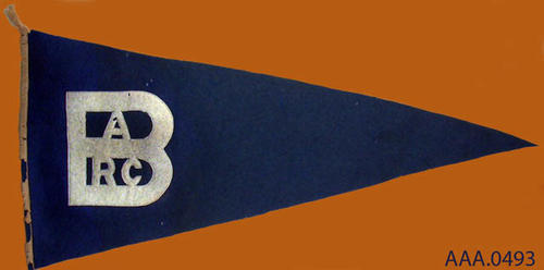 "This artifact is a blue pennant with a white base.  It measures 26 1/4"" x 13 1/2"".  The white letters on the blue background read:  ""BARC."""