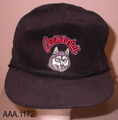 "Tis artifact is a black baseball hat.  A small logo is on the front of the cap.  The word ""Centennial"" is arched over the picture of a Husky which is the school's mascot."